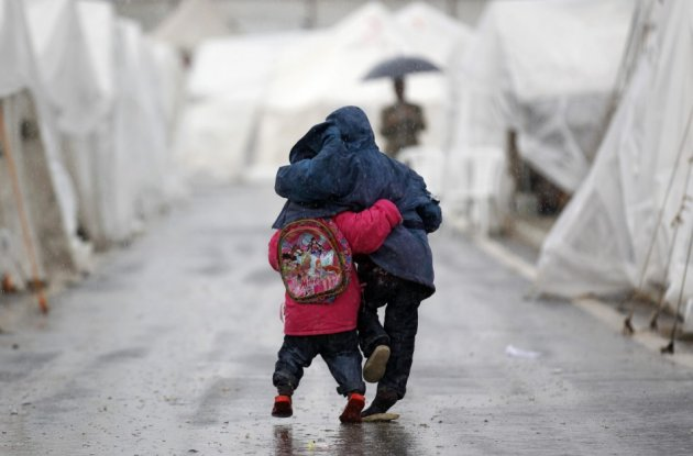 Syrian boys walk shoulder to shoulder in the rain at the Boynuyogun refugee camp on the Turkish-Syrian border in Hatay