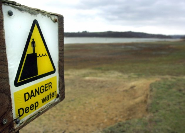 A sign warning of deep water is seen some distance from the water's edge at Bewl Reservoir, Kent (Reuters)