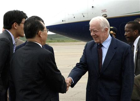 Former U.S. President Jimmy Carter shakes hands with Kim Kye-gwan, Vice Foreign Minister of North Korea, upon his arrival at Sunan airport in Pyongyang