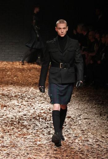 A model wearing a tartan dress walks the ramp