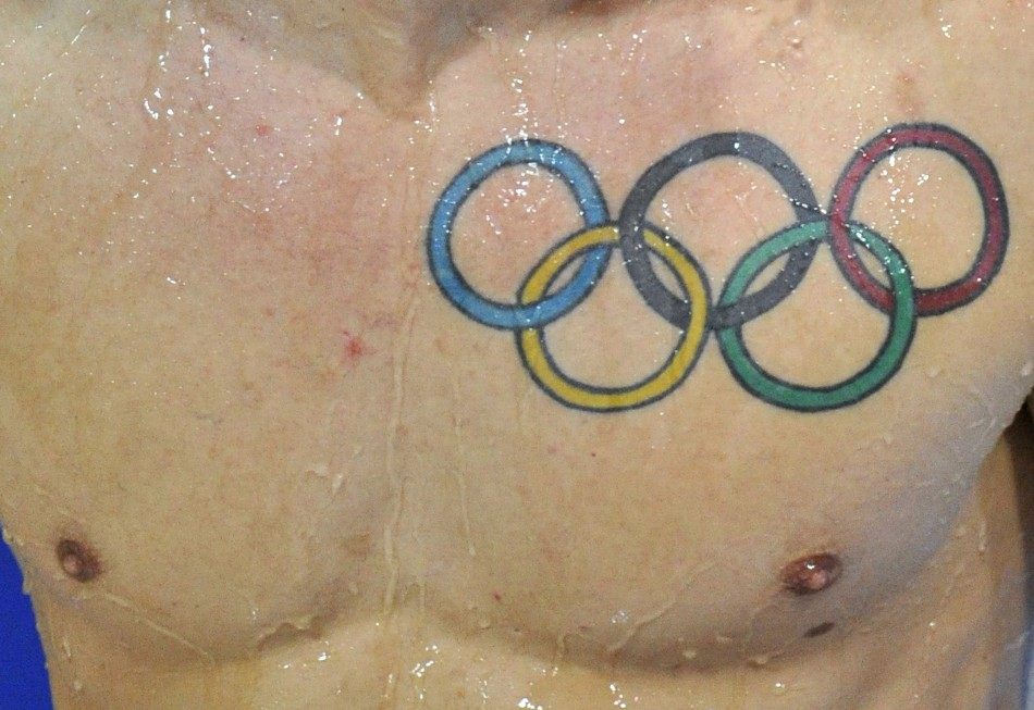 A tattoo of the Olympic rings is seen on Baker of Britain after he dives during the Men's Synchronised 3m Springboard preliminary round at the FINA Diving World Cup in London