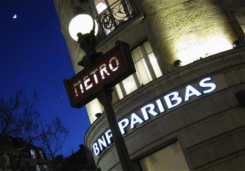 The Paris headquarters of the BNP Paribas bank is seen near a Paris Metro sign