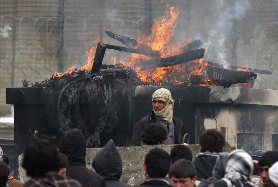 Afghan men stand near a pile of wood and tyres, set on fire by the protesters, during a protest outside the U.S. military base in Bagram