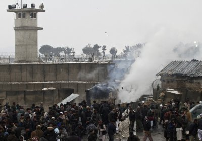 Afghan men gather as some of them throw rocks towards the U.S. military base during a protest in Bagram