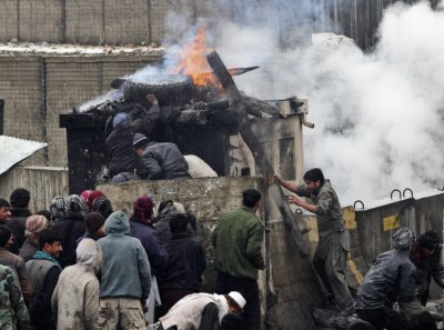 Afghan men stand near pieces of wood and tyres which they set on fire during a protest outside the U.S. military base in Bagram, north of Kabul