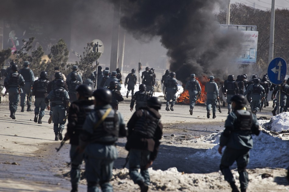 Afghan policemen march towards protesters during a protest near a U.S. military base in Kabul