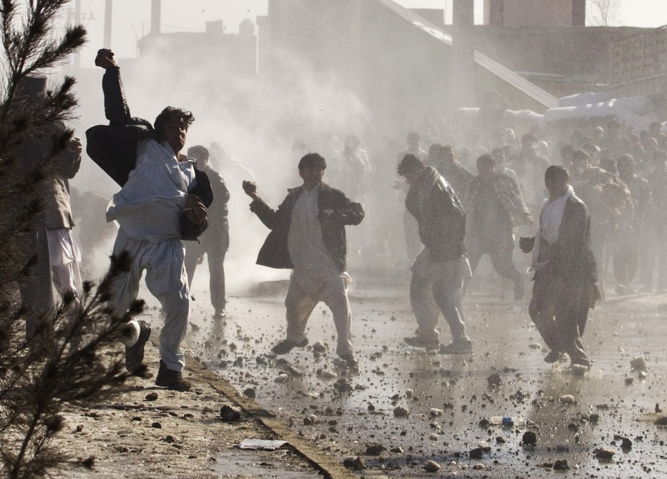 Afghan protesters throw rocks towards a water canon near a U.S. military base in Kabul