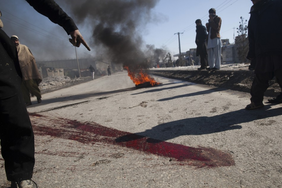 An Afghan man points to blood on a street during a protest near a U.S. military base in Kabul