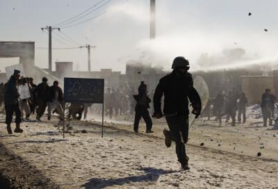 An Afghan policeman runs away as protesters throw rocks near a U.S. military base in Kabul