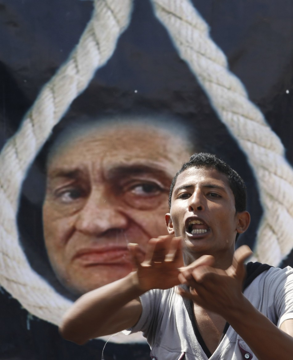 An anti-Mubarak protester shouts slogans in front of a poster depicting Mubarak with a noose in Cairo