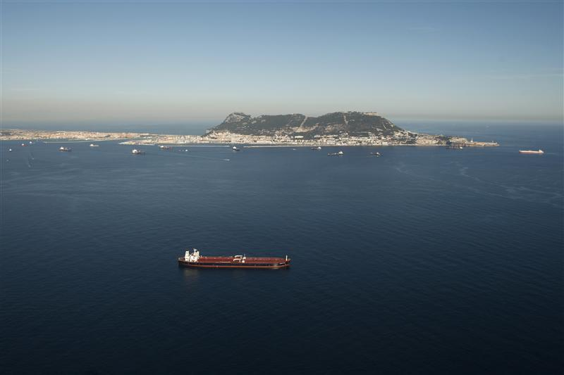 Aerial view shows a merchant marine ship sailing past the Rock of Gibraltar in the Strait of Gibraltar