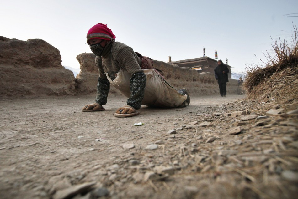 Tibetan woman prostrates as she pray near the Labrang Monastery in Xiahe county, Gansu Province