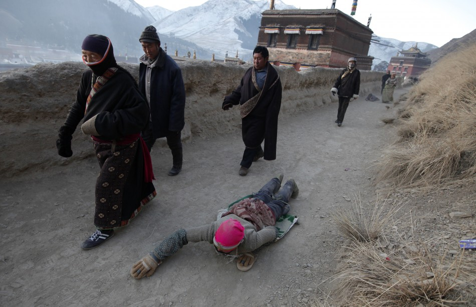 An ethnic Tibetan woman prostrates as she prays near the Labrang Monastery in Xiahe county, Gansu Province