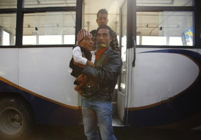 Dangi, 72, who claims to be the world039s shortest man standing at a height of 22 inches, is carried by his relative at Tribhuvan International Airport upon his arrival in Kathmandu
