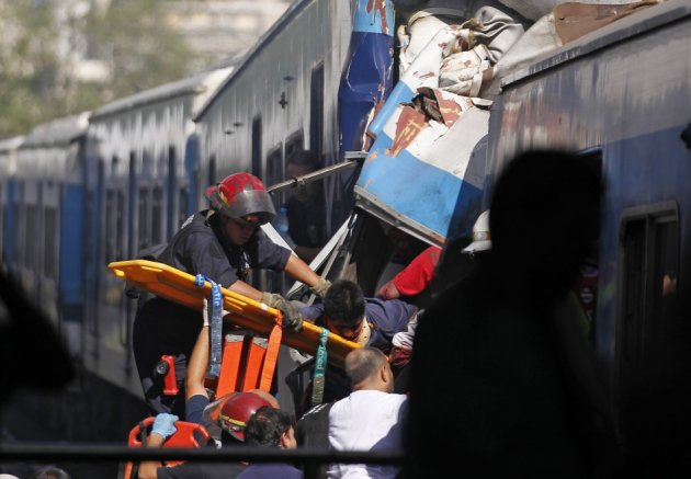 Rescue workers extract a passenger from a commuter train that crashed in Buenos Aires (Reuters)