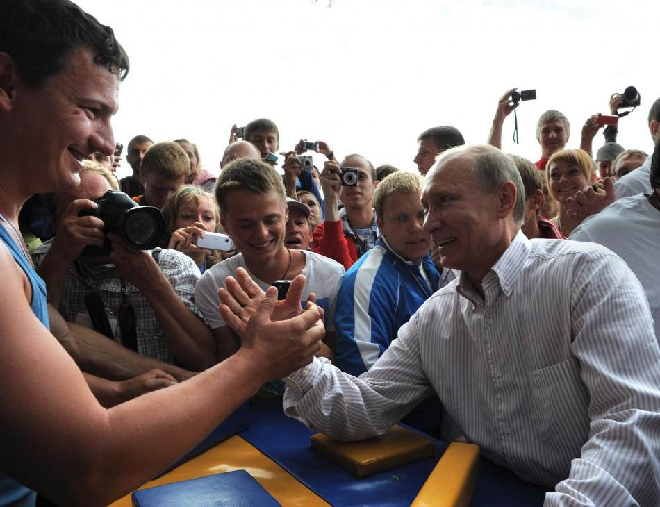 Russian Prime Minister Vladimir Putin (R) arm-wrestles Nashi