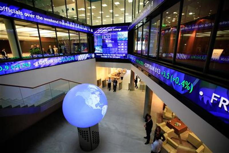 Financial data and news headlines stream accross ticker screens around the atrium of the London Stock Exchange