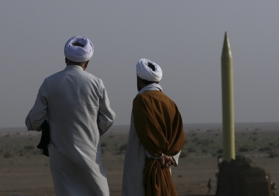 Iranian clerics stand near surface to surface missile which is ready to be launched during war game near city of Qom