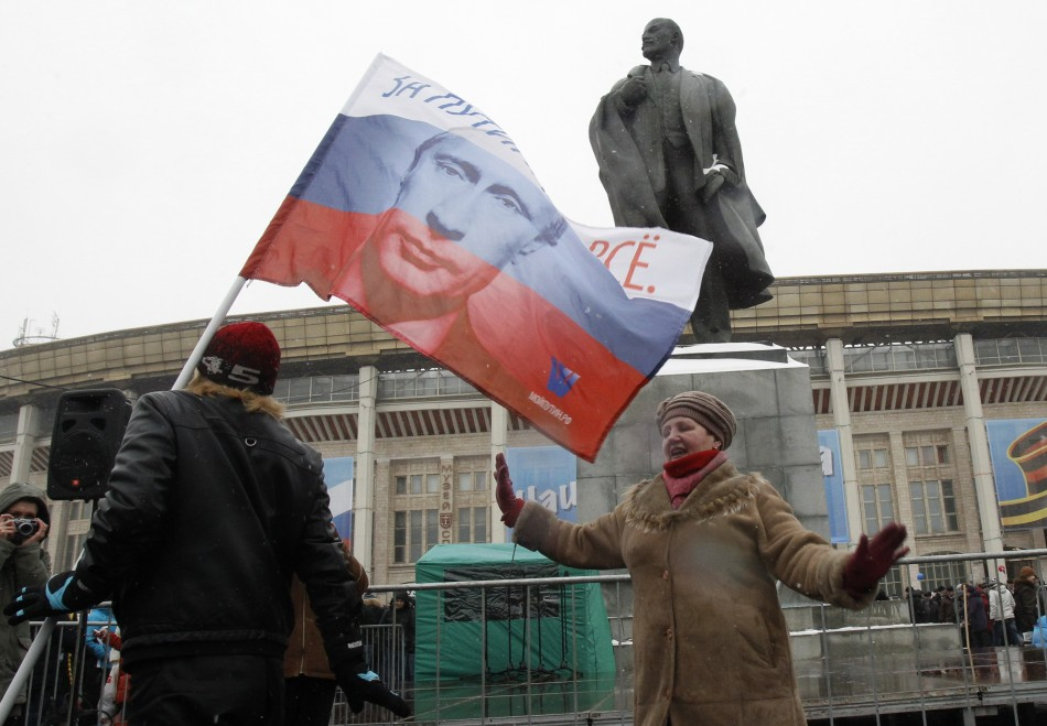 Woman dances outside stadium in front of statue of Vladimir Lenin, founder of Soviet state