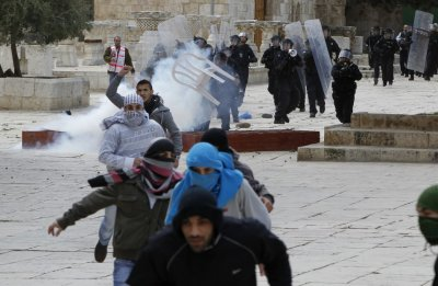 Palestinian protesters run away from Israeli policemen