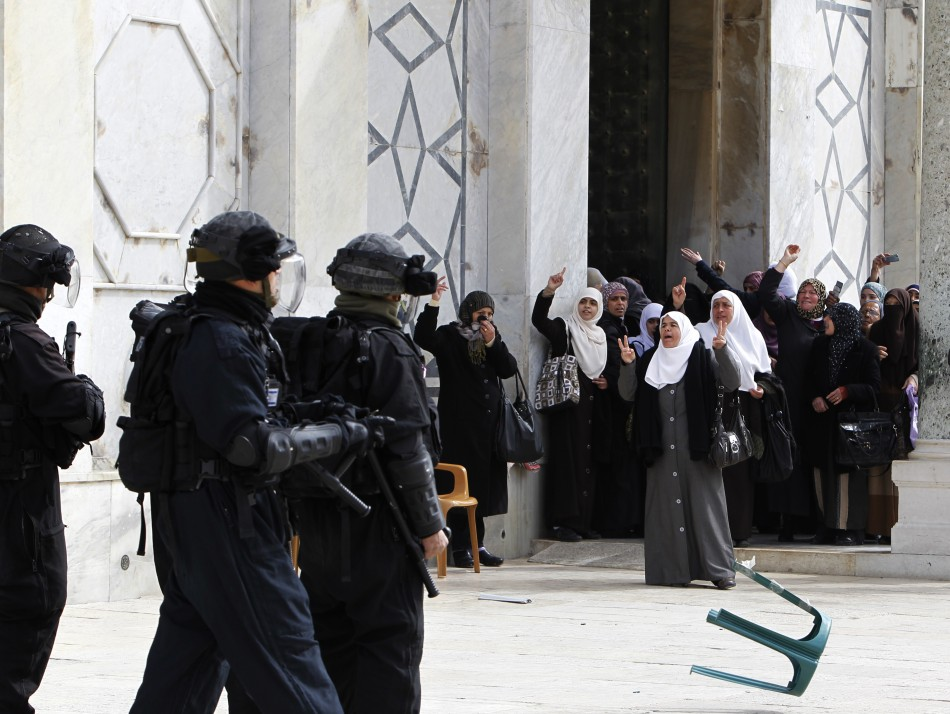 Palestinian women gesture as they shout at Israeli policemen