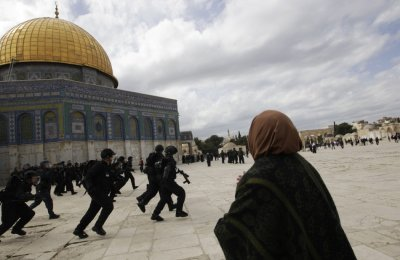 A Palestinian woman gestures at Israeli policemen as they run with their weapons during clashes with Palestinian protesters at the Temple MountNoble Sanctuary