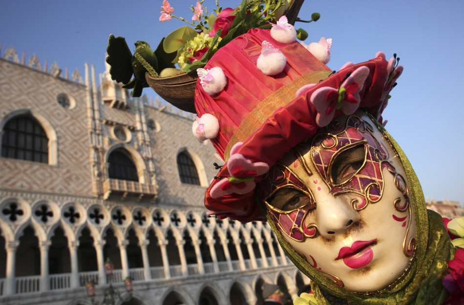A masked reveller poses in Saint Marks Square