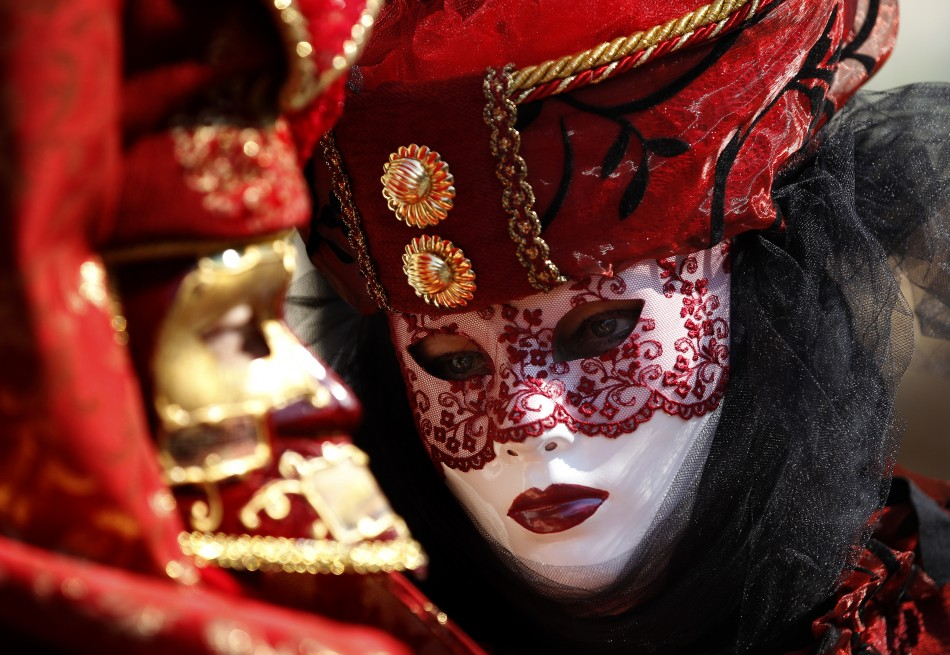 Masked revellers pose in Saint Mark's Square