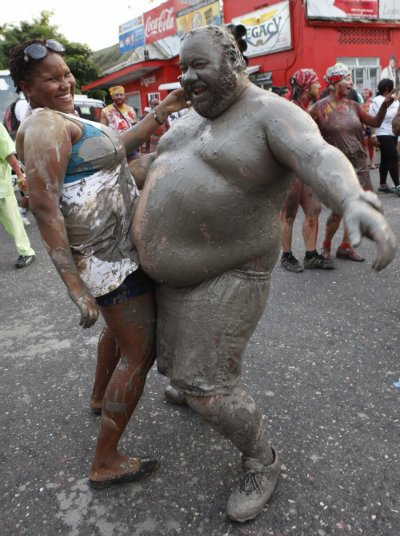 People covered in mud dance during Jouvert celebrations