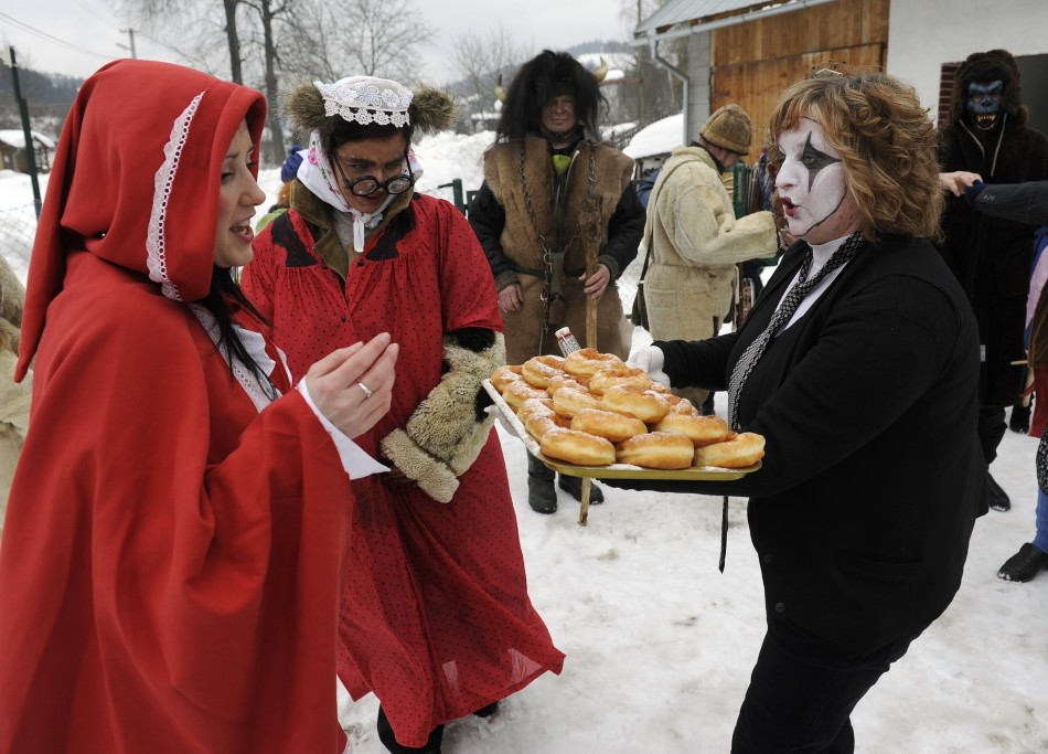 A villager dressed in a mime costume serves donuts to others during a carnival in the village of Lazy pod Makytou