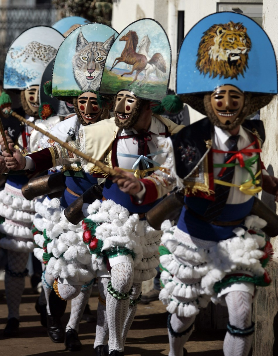 "Revellers dressed as ""Peliqueiros"" run through a street during a carnival in Spain's northwestern village of Laza"