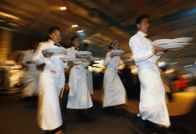 Waiters hold food during a gala dinner