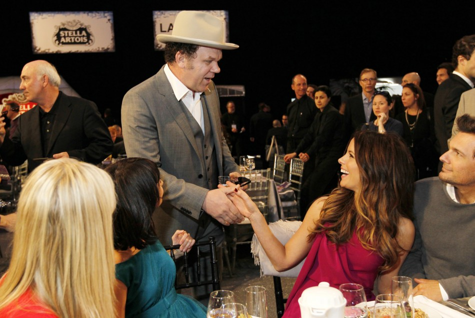 Actor John C. Reilly shakes hands with actress Kate Beckinsale (R)