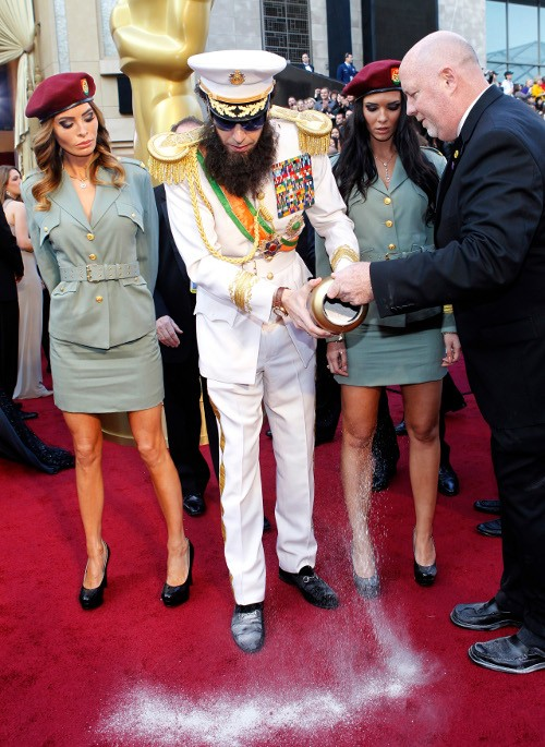 "Cohen arrives in character from his upcoming film ""The Dictator"" while dumping the contents of an urn with a picture depicting   North Korea's late leader Kim Jong-il on it at the 84th Academy Awards in Hollywood"