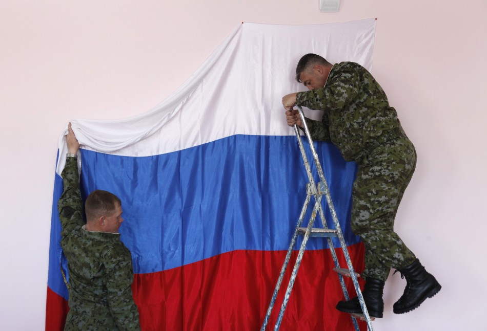 Russian soldiers hang their national flag at a polling station