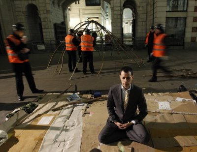 A protester meditates in front of a statue of Buddha as bailiffs dismantle the frame of his tent behind him during the eviction of the Occupy encampment outside St Paul039s Cathedral in London