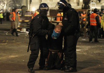 A protester is detained by the riot police after being removed by bailiffs from the last remaining structure of the Occupy encampment outside St Paul039s Cathedral in London