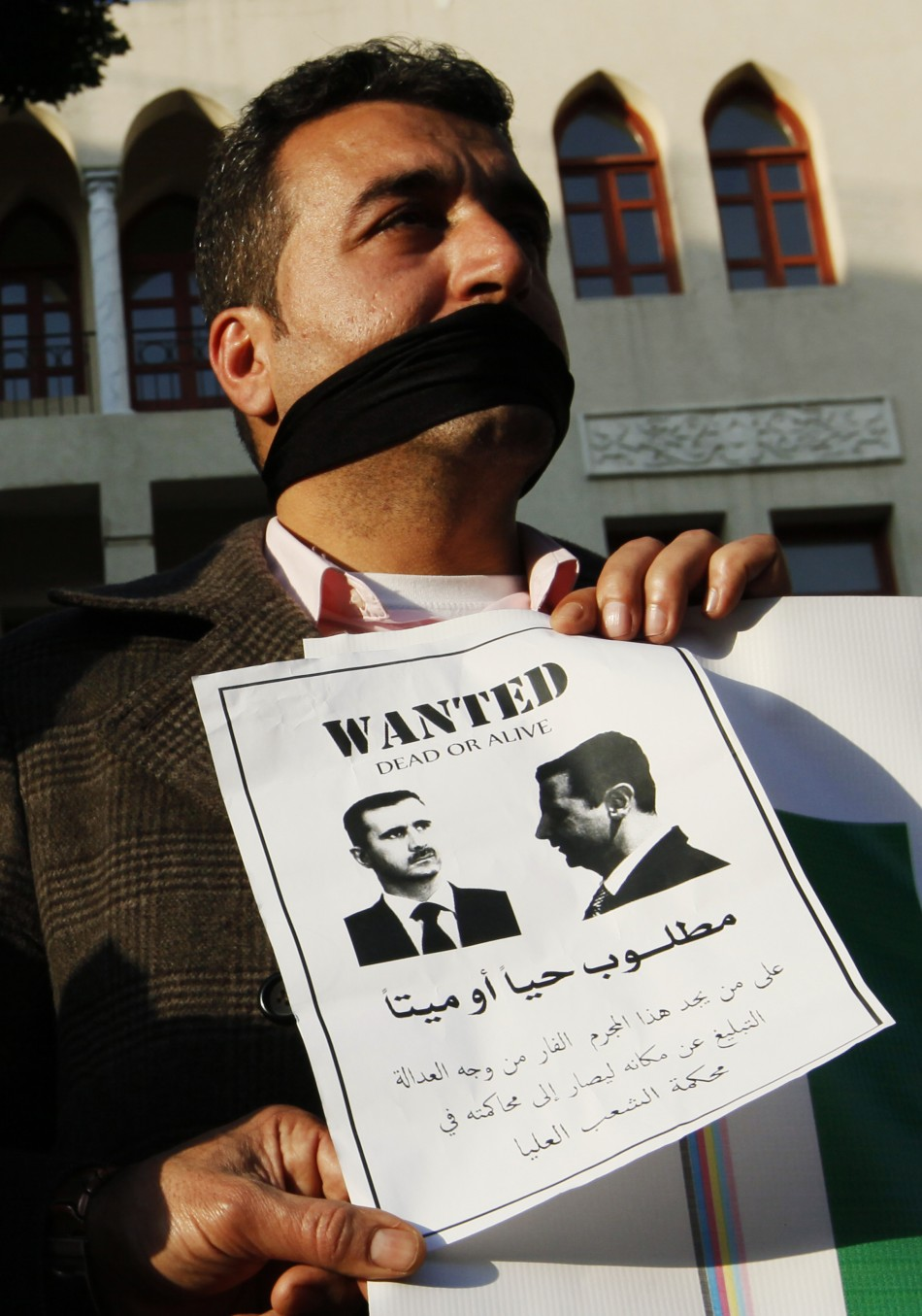 A Syrian man living in Lebanon carries a sign as he protests against Syrian President Bashar al-Assad during a sit-in demonstration in Beirut