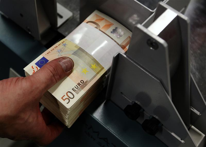 An employee at the Belgian Central Bank adjusts fifty-euro notes with a machine in Brussels