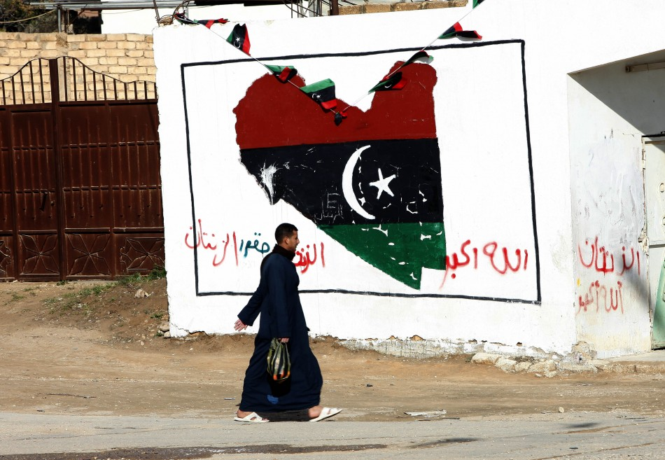 A man walks past a wall painted with a graffiti with colours of the ruling National Transitional Council in Zintan