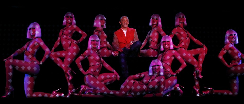 Designer Christian Louboutin poses with dancers during the press presentation of the new revue named Feu at the Crazy Horse in Paris