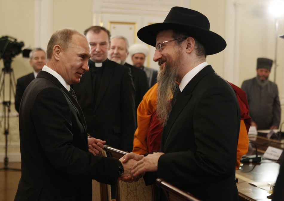 Russian PM Putin shakes hands with Russia's Chief Rabbi Lazar during his meeting with religious leaders in Moscow