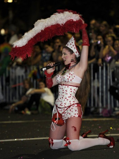 A woman sings a song as she moves along with the parade during the 2011 Gay and Lesbian Mardi Gras in Sydney, Australia Saturday, March 5, 2011