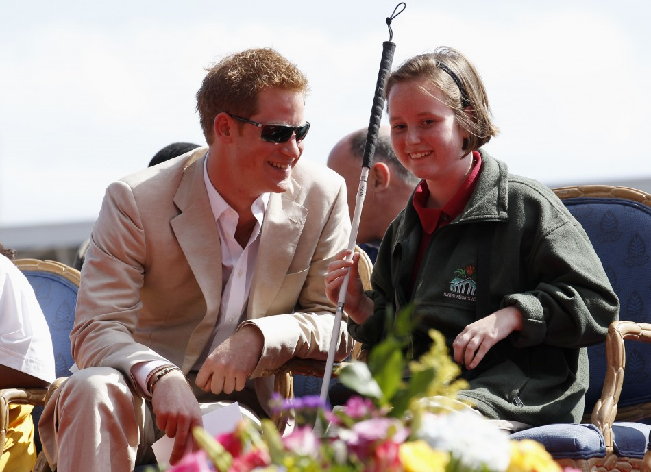 Britain's Prince Harry talks to Anna Albury as he attends a youth rally and cultural show at the National Stadium in Nassau