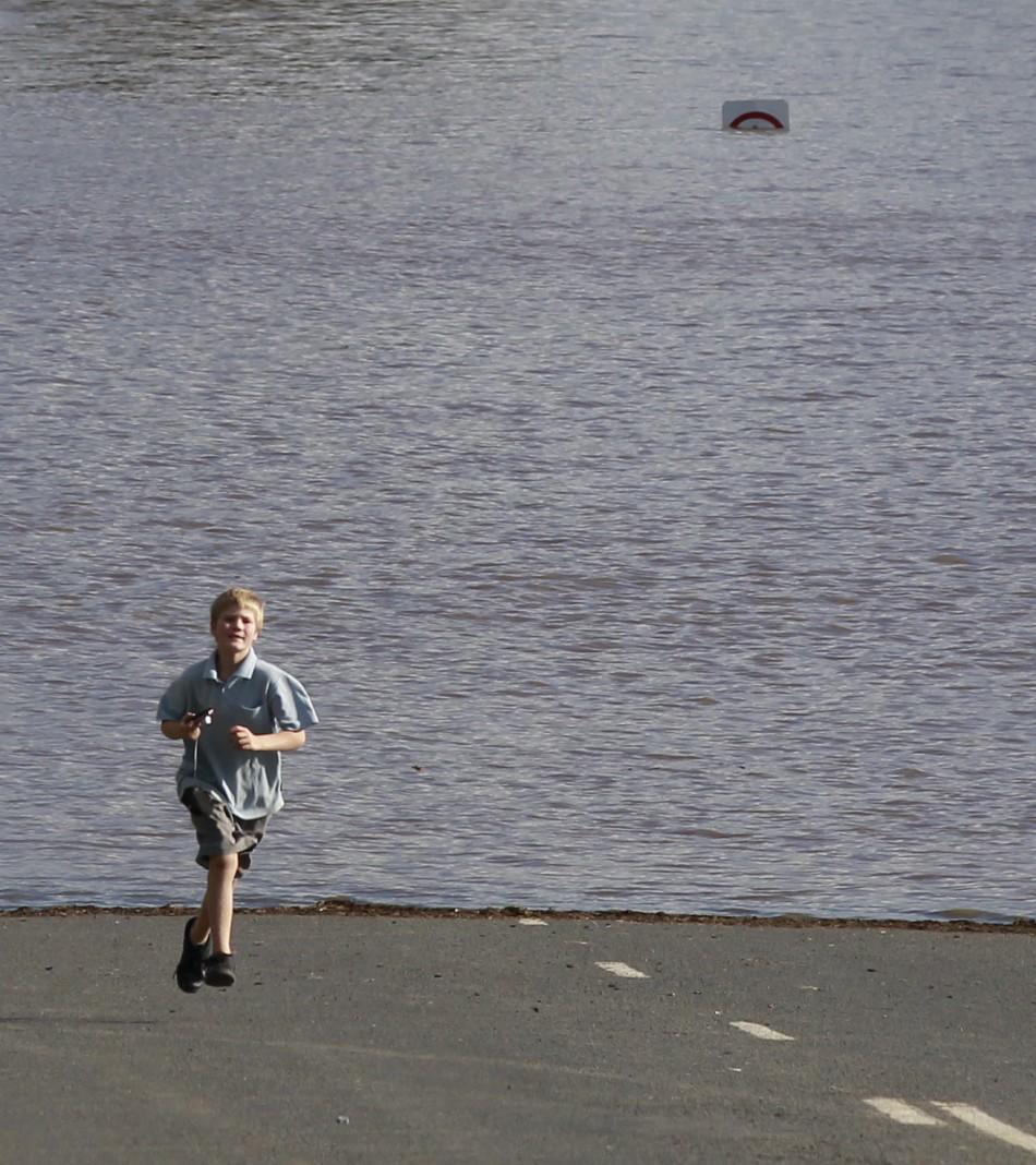 A local boy plays next to a road submerged in flood waters near Wagga Wagga