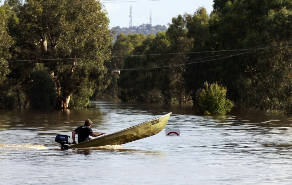 A man drives a boat on a road submerged in flood waters near Wagga Wagga