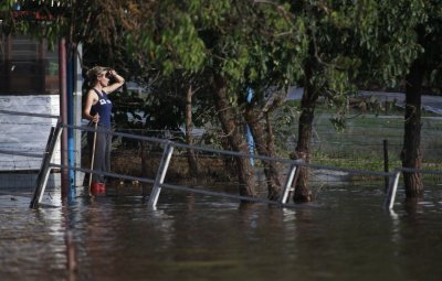 A woman looks out from her house surrounded by flood waters in Wagga Wagga