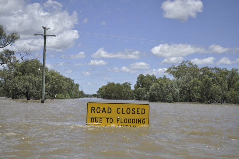 A flood warning sign starts to disappear below floodwaters near Charleville