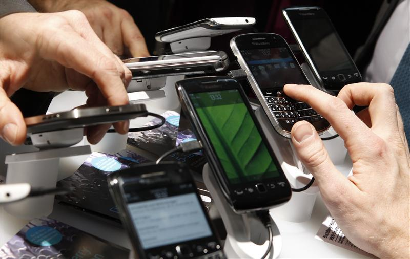 Visitors inspect Blackberry mobile phones at their booth at the CeBit computer fair in Hanover