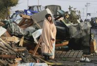 In Ishimaki City, a woman looks at the damage caused by a 2011 tsunami and earthquake